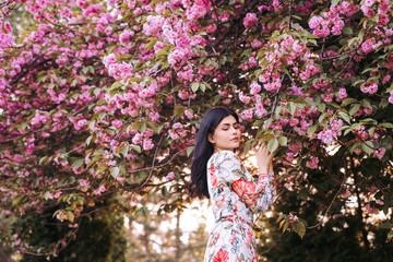 Fascinating tender woman standing next to pink blooming tree in garden