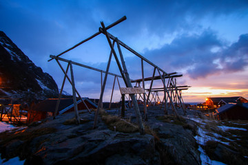 Wooden codfish drier in the small fishing village of A (Moskenes) at the end of the road of the Lofoten islands archipelago in northern Norway - Red rorbuer on stilts in winter at dawn in a fjord