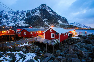 Small fishing village of A (Moskenes) at the end of the road of the Lofoten islands archipelago in northern Norway - Red rorbuer on stilts in winter at dawn in a fjord