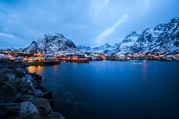 Panoramic overview of the small fishing village of A (Moskenes) at the end of the road of the Lofoten islands archipelago in northern Norway - Red rorbuer on stilts in winter at dawn in a fjord