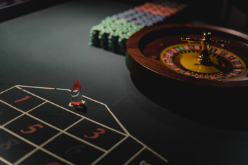 Roulette table with chips in casino. Roulette wheel in the foreground. Gamble game.