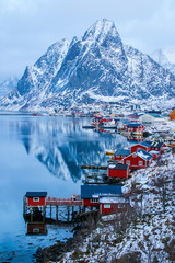 Rorbuer in Reine in the Lofoten Islands in winter - View over a snowy mountain on a cloudy day with an alignment of fishing huts along the coast of some placid waters