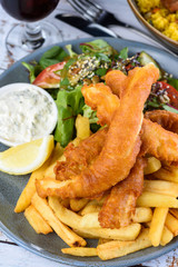 A plate of 'Fish and Chips' with battered fish, potato chips, salad, tartar sauce and lemon wedge.