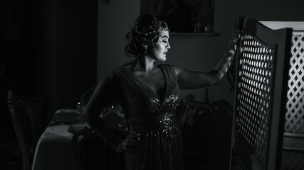 black and white photo with a woman with a diadem long gloves and a shiny dress standing at the screen