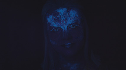 Woman with a glowing blue face looks at the camera