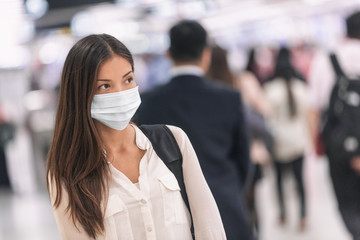 Virus mask Asian woman travel wearing face protection in prevention for coronavirus in China. Lady walking in public space bus station or airport. Wall mural