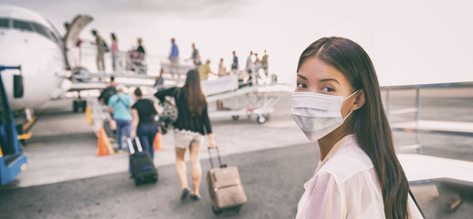 Airport Asian woman tourist boarding plane taking a flight in China wearing face mask. Coronavirus flu virus travel concept banner panorama. Fotomurales