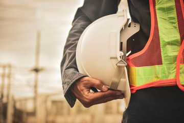 Close up hand holding white helmet hard hat Engineering concept