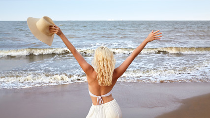 Blonde Woman in White Summer Style Standing at Sea and Holding Hat. Luxury Lifestyle Rear View. Summer Vacation Concept