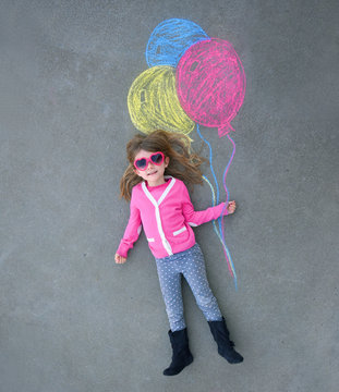 Child Holding Colorful Chalk Balloons on Sidewalk