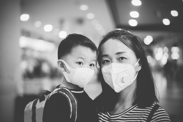 Coronavirus and Air pollution pm2.5 concept.Little chinese boy and chinese mother wearing mask for protect pm2.5 in airport terminal.Wuhan coronavirus and epidemic virus symptoms.black and white.