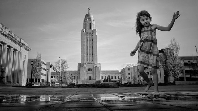 Cute Girl Playing On Wet Footpath Against Sky
