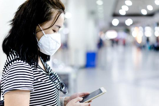 Coronavirus and Air pollution pm2.5 concept.Chinese woman read coronavirus news in airport terminal wearing mask for protect virus and pm2.5.Wuhan coronavirus and epidemic virus symptoms.
