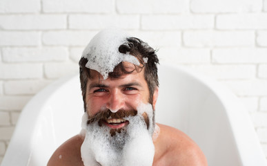 Taking bath with soap suds. Brutal muscular man in bathroom. Man style and fashion concept. Soap beard.