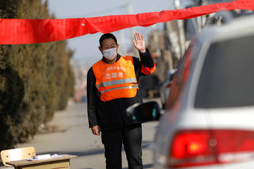 A village committee member wearing face mask and vest, stops a car for checking as he guards at the entrance of a community to prevent outsiders from entering, as the country is hit by an outbreak of the new coronavirus, in Tianjiaying village