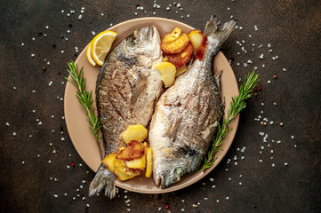 grilled dorado fish and fried potatoes on a plate with spices and lemon on a stone background