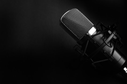 Condenser black studio microphone on a black background. Streamer, podcasts, music background