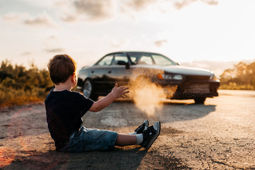 the boy sprinkles magic dust, conjures and his dream of a real car comes true, the child throws dust at sunset in a beautiful backlight Wall mural