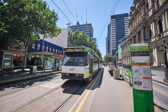 A typical Melbourne Tram scene with tourists and locals at a tram station waiting for public transport