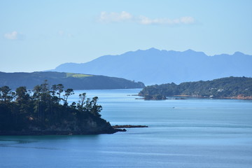 Bays and peninsulas of Mahurangi Harbour with hilly landmass in background on very calm day.