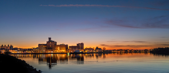 Fotomurales - RIVER BY ILLUMINATED BUILDINGS AGAINST SKY AT SUNSET