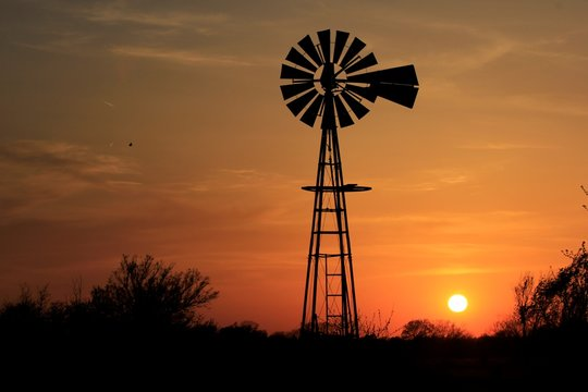 silhouette of windmill at sunset with a colorful sky in Kansas