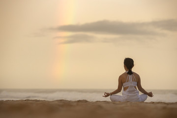 Garden Poster Lotus flower Yoga lotus pose meditation practice of young Asian female on an beach with rainbow background.