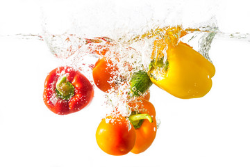Three bell peppers, tomato and cucumber fall into the water with splashes, isolated on a white background.