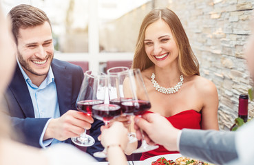 People sitting on restaurant table toasting with red wine