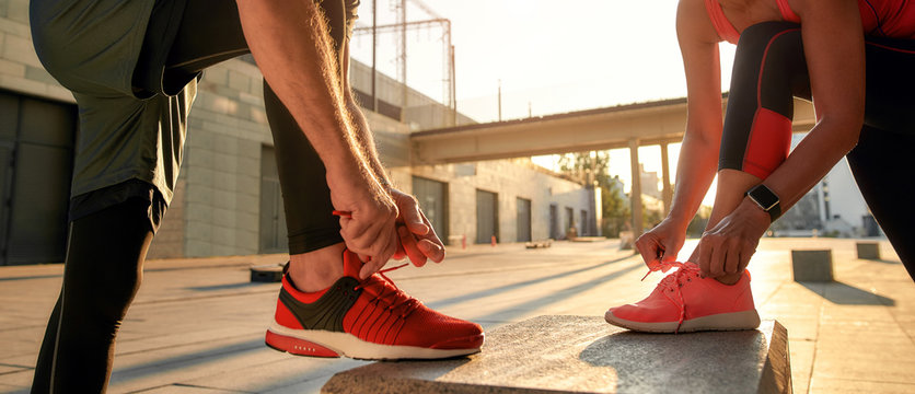 Active morning. Close up photo of two people in sport clothes tying shoelaces before running together outdoors