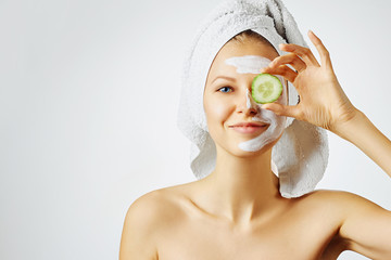 Fototapeta Cosmetology, skin care, face treatment, spa and natural beauty concept. Woman with facial mask holds slices of cucumber. obraz