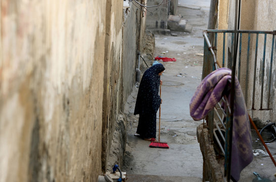 A Palestinian woman sweeps the floor outside her home at Beach Refugee camp in Gaza City
