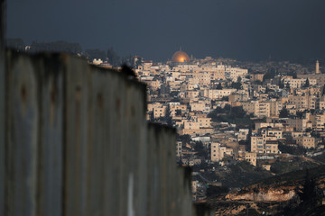 A general view picture shows the Dome of the Rock in Jerusalem's Old City in the background and part of the Israeli barrier in the foreground, as seen from the Palestinian town of Abu Dis in the Israeli-occupied West Bank, east of Jerusalem