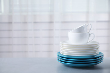 Set of clean tableware on light grey table. Space for text