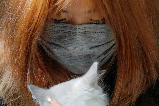 A person wearing a face mask holds a cat on Swanston Street after cases of the coronavirus were confirmed in Melbourne