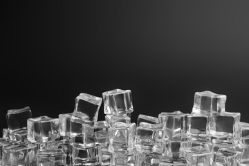 Crystal clear ice cubes on black background. Space for text
