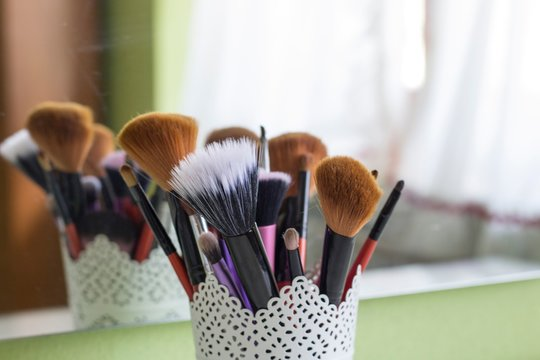 Close-Up Of Various Make-Up Brushes In Desk Organizer