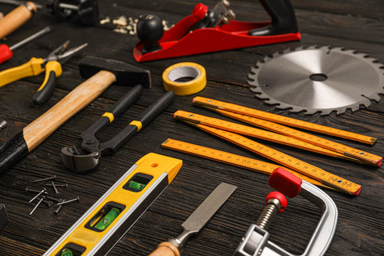 Different carpenter's tools on black wooden background