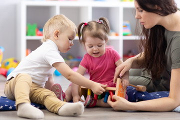 Preschooler children playing with educational wooden toys at kindergarten or daycare center. Toddlers with teacher in nursery.