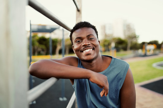 Smiling portrait of a sporty young african american man leaning on bar at the public park looking to camera with a big smile