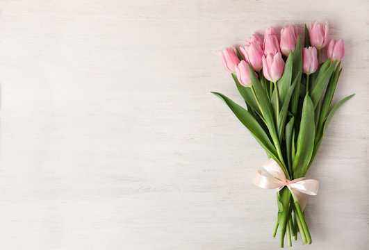 Beautiful pink spring tulips on white wooden background, top view. Space for text