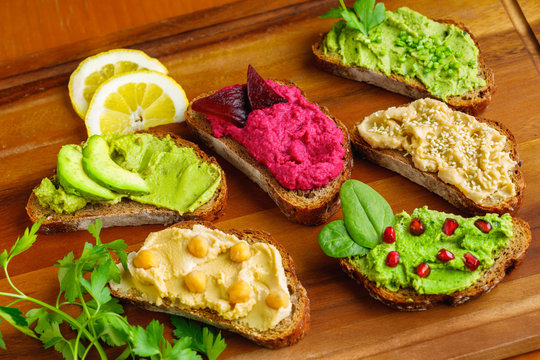 Different kinds of dips bread with humus. Traditional with chickpeas and sesame seeds , herbs with spinach leaves, avocado and beetroot hummus,