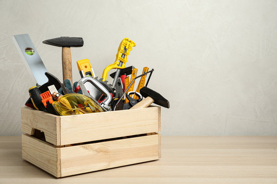 Crate with different carpenter's tools on wooden table. Space for text