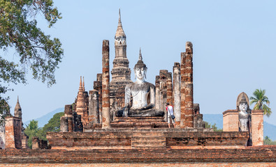 Tourist take pictures of ancient Buddha statue at sunrise in Ayutthaya, Thailand; travel and tourism concept