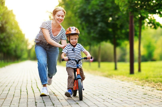 happy family mother teaches child son to ride a bike in the Park