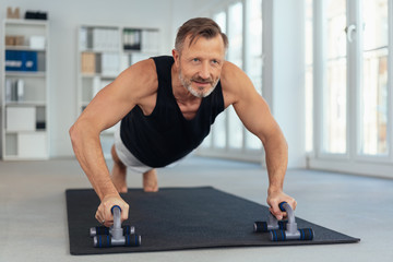 Middle-aged man exercising on handles for push-ups Wall mural