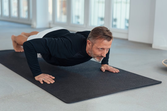 Man working out doing press ups in a gym