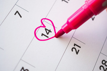 Female Hand with pen mark heart shape on calendar date at 14th valentine day