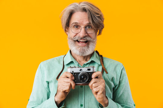 Positive grey-haired man photographer holding camera.