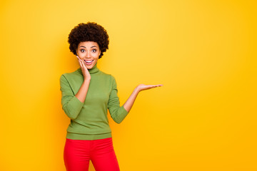 Photo of curly cheerful cute pretty nice girlfriend in red pants holding empty space on hand smiling toothily emotionally isolated yellow vivid color background